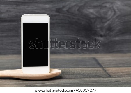 Smartphone and wood spoon on wooden table. Concept online food, Eating technology. - stock photo