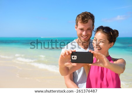 Smartphone - beach vacation couple taking selfie photograph using smartphone relaxing and having fun holding smart phone camera. Young beautiful multicultural Asian Caucasian couple on summer beach. - stock photo