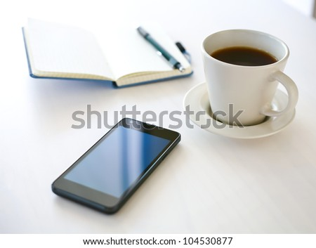 Smartphone close-up, coffee and planning book on the background - stock photo