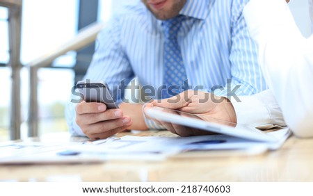 Smartphone handheld in closeup, colleagues working in background.  - stock photo