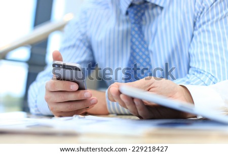 Smartphone handheld in closeup, colleagues working in background - stock photo