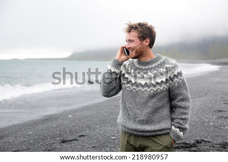 Smartphone man talking on smart phone walking on black sand beach on Iceland wearing Icelandic sweater. - stock photo