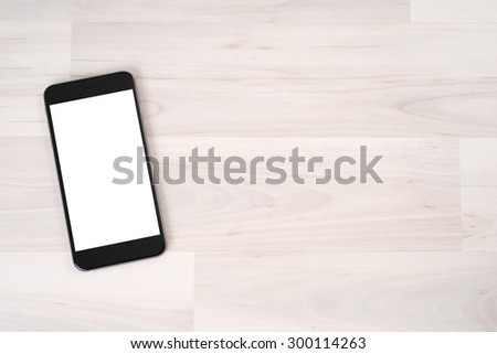 Smartphone on wooden table on light background - stock photo