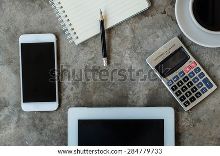 Smartphone, Table, notepad , pencil ,calculator and coffee on concrete table background - stock photo