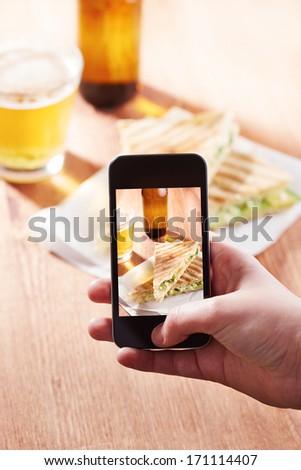 Smartphone taking photo of feta cheese sandwich on a restaurant - stock photo