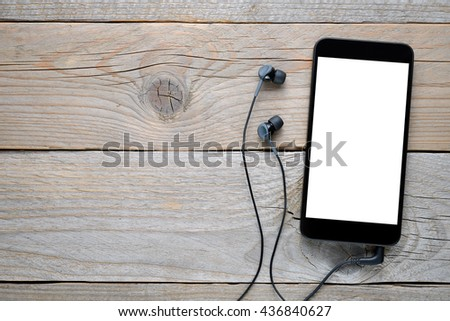 Smartphone with headphones on wooden background - stock photo