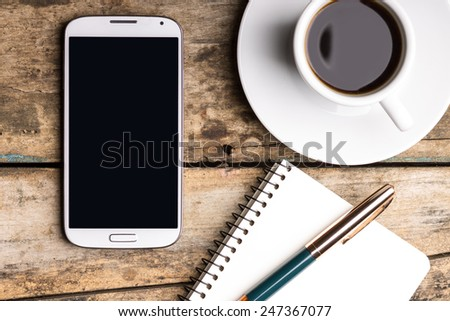 Smartphone with notebook and cup of strong coffee on wooden background. Cell phone with writing set with espresso - stock photo