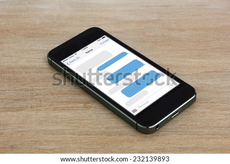 smartphone with sms chat on a screen lying on wooden table, iphon style - stock photo