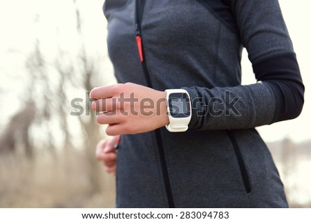 Smartwatch woman running with heart rate monitor. Closeup of female wrist wearing smart sport watch as activity tracker outdoors during cardio workout. - stock photo