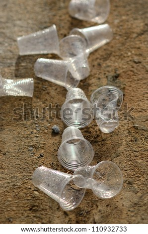 Smashed and used plastic cups being thrown on the ground. - stock photo