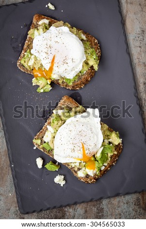 Smashed avocado and feta cheese toast with poached eggs.  Overhead view, on dark slate. - stock photo