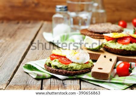 smashed avocado, tomatoes, egg sandwich. toning. selective focus - stock photo