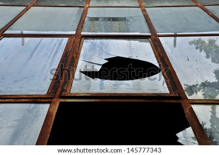 Smashed rusty windows of a decayed building. Abstract grunge background. - stock photo