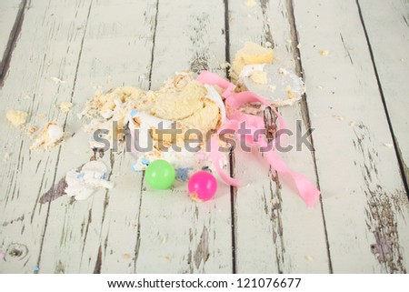Smashed up birthday cake taken at end of party and messing the antique distressed wooden floor - stock photo