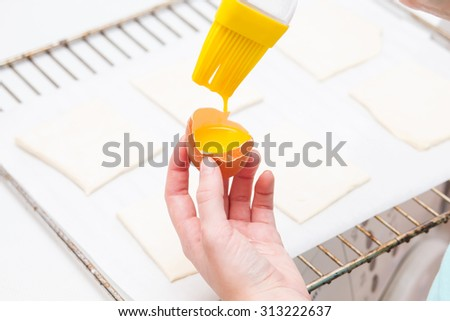 Smearing egg pie. Cooking sweet pastries. Hands - stock photo