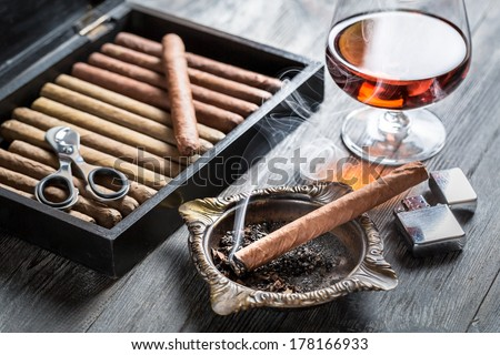 Smell of brandy and smoking a cigar - stock photo