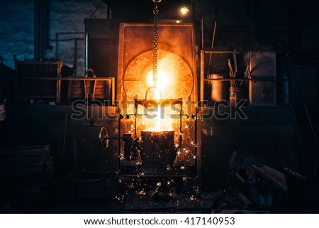 Smelting metal in a metallurgical plant. Liquid iron from metal ladle pouring in castings at factory - stock photo