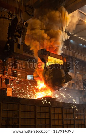 Smelting metal in a metallurgical plant. Liquid iron in the ladle in metallurgy factory. - stock photo