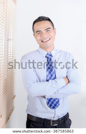 Smile asian business man standing in office - stock photo