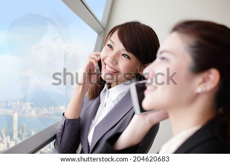 Smile Business woman speaking phone and looking through window with city background, asia, hong kong, asian - stock photo