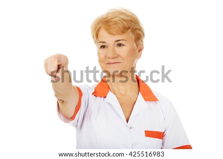 Smile elderly female doctor or nurse pointing at camera - stock photo