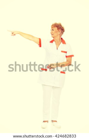 Smile elderly female  doctor or nurse pointing for copyspace or something - stock photo