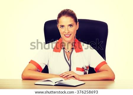 Smile female doctor or nurse sitting behind the desk - stock photo
