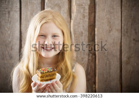 smile girl with cake on wooden background - stock photo