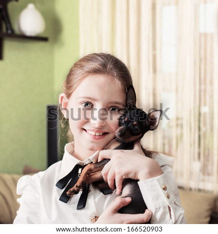 smile girl with toy terrier - stock photo