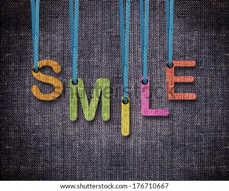 Smile Letters hanging strings with blue sackcloth background. - stock photo