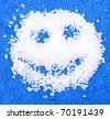 Smile made of bath salt on blue towel - stock photo