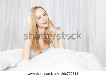 Smile of young Caucasian woman on the bed - stock photo