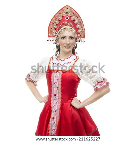 Smile young woman hands on hips portrait  in russian traditional costume --  red sarafan and kokoshnik. Studio shot isolated on white. - stock photo