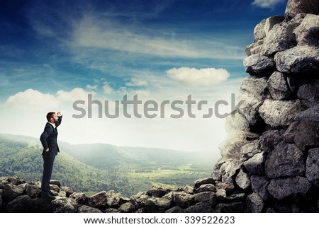 smiley businessman holding his hand near brow and looking up at stone mountain - stock photo