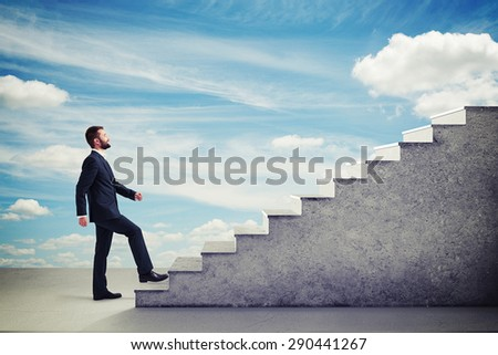 smiley businessman in formal wear walking up stairs over blue sky - stock photo
