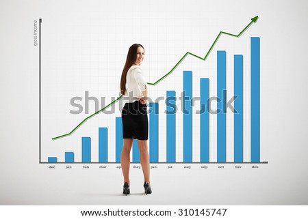 smiley businesswoman with big graph with positive dynamics over light grey background - stock photo