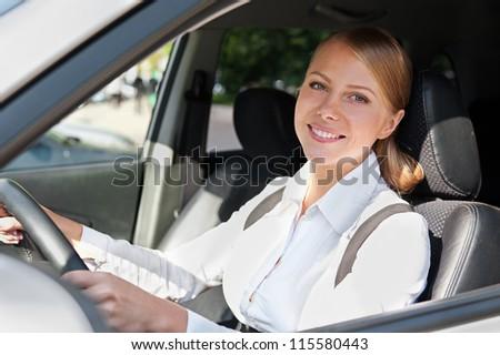 smiley caucasian female in the car - stock photo
