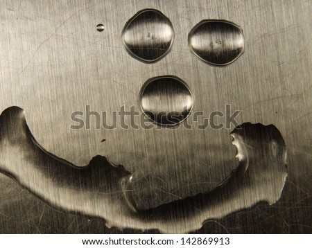 Smiley face formed of water droplets on sheet metal background. - stock photo