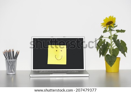 Smiley face on laptop screen by pencils in cup and flowers on desk - stock photo