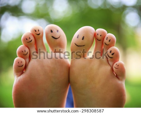 smiley faces on a pair of feet on all ten toes (VERY SHALLOW DOF - big toe on the right) in a park setting  - stock photo