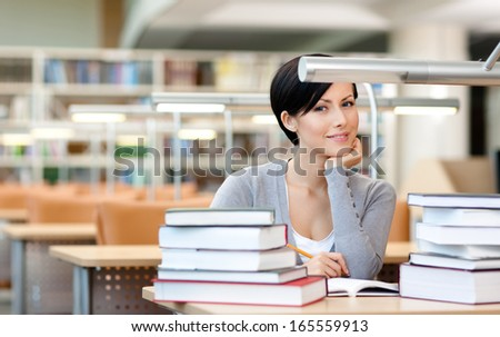 Smiley female student studies with piles of books sitting at the desk at the library - stock photo