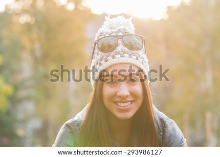 Smiley girl in a park with sun flare. - stock photo