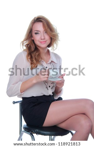 Smiley girl is holding coffee cup and sitting on a stool - stock photo