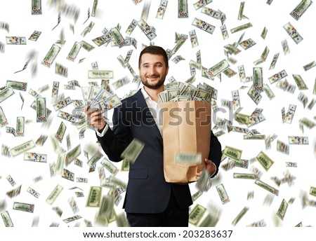 smiley glad businessman standing under money rain, holding big paper bag and showing dollar's - stock photo