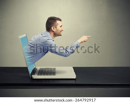 smiley handsome man got out of the laptop and pointing at empty copyspace against dark background - stock photo