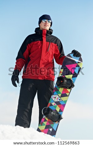smiley happy young sportsman with snowboard at winter outdoor - stock photo