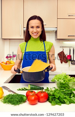 smiley housewife holding the pan with spaghetti in the kitchen - stock photo