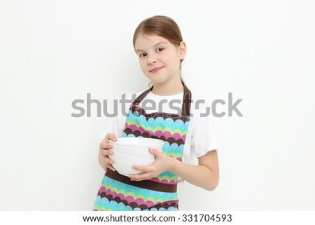 Smiley little girl holding white bowls - stock photo