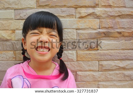 Smiley little girl standing at brick wall background, selective focus - stock photo