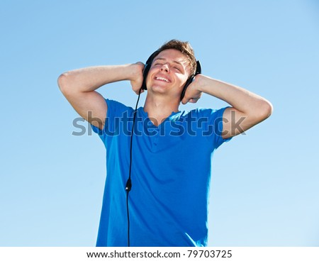 smiley man in headphones listening music with pleasure against blue sky - stock photo